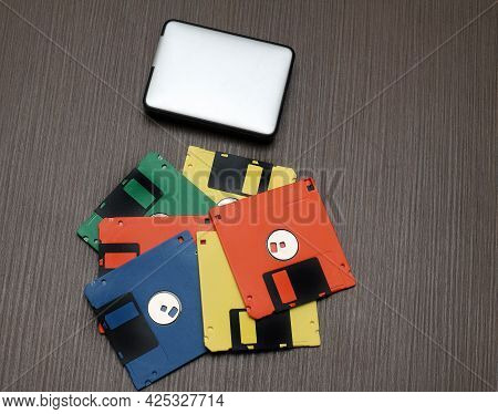 Old Colorful Retro Floppy Disks And Modern External Hard Drive On Wooden Table
