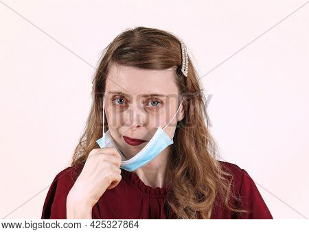Young Beautiful Woman With Dark Red Lipstick Taking Off Medical Protective Face Mask
