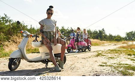 Beautiful Young African American Woman Resting On Retro Scooter Outdoors In Warm Sunny Day With Comp