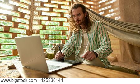Side View Of A Man Drawing With Stylus On Tablet, He Is Sitting In Forest House, Looking At Monitor