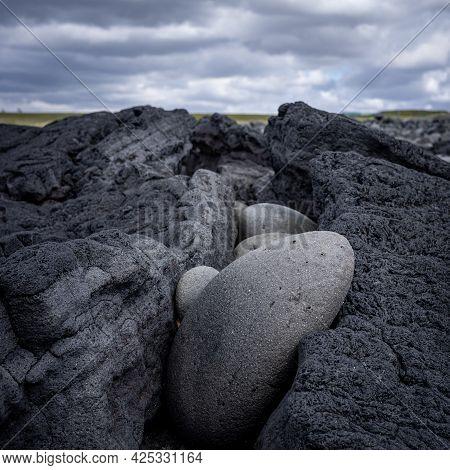 Lava Stones Fitted In A Fissure In A Big Lava Rock, Blurred Cloudy Background, Hvaleyri Beach, Icela