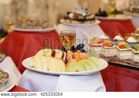 Catering Plate With Sliced Fruit Apples, Pears, Tangerine Slices, Grapes And A Glass Of Apple Juice