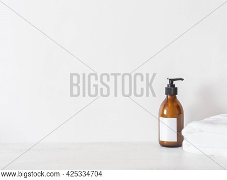 Cosmetic Amber Glass Bottle With White Lable And White Towels On White Background. Front View. Minim