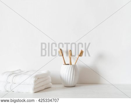 Minimal Bath Background With Bamboo Toothbrushs In Ceramic Glass And White Towels On White Backgroun