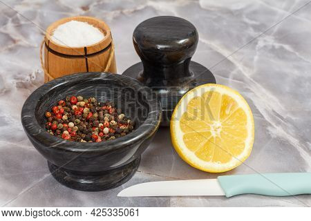 Wooden Salt Cellar, A Stone Bowl With Peppercorn And A Lemon On The Kitchen Table. Shallow Depth Of