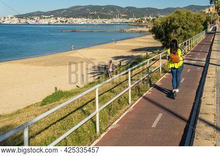 Palma De Mallorca, Spain; June 25 2021: Person Driving An Electric Scooter Along The Promenade Of Pa