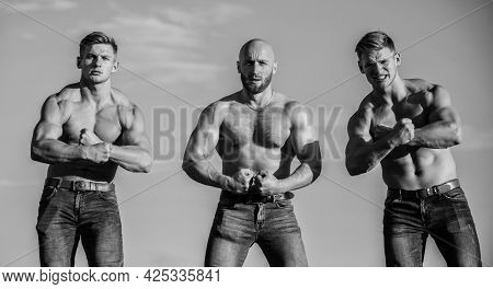 Gym Trainer. More Strength More Muscle. Strong Men Blue Sky Background. Showing Abs Biceps. Group Mu
