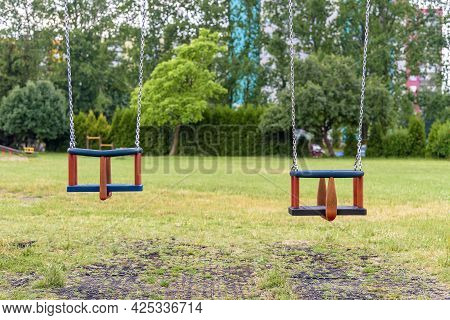 Two Empty Swings With Chains On The Playground
