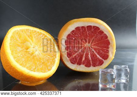 Orange And Grapefruit In The Cut Lie Next To Ice Cubes On A Black Background. Fruit For Lemonade. Ci