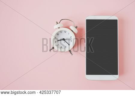 White Mobile Phone With Clipping On Touchscreen And Analog Alarm Clock On Sweet Pastel Pink Backgrou