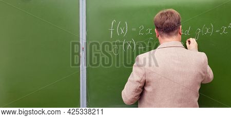 A Math Teacher Shows Students The Solution Of A Problem At The School Blackboard. Copy Space
