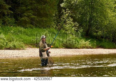 Perm Krai, Russia - June 17, 2021: Fisherman Catches A Grayling With A Spinning Rod On The Usva Rive