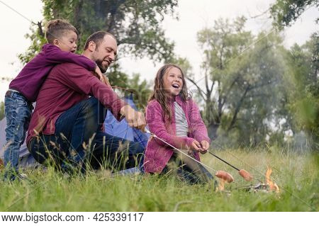 Father, Daugther And Son Roasting Sausages At Campfire In Forest