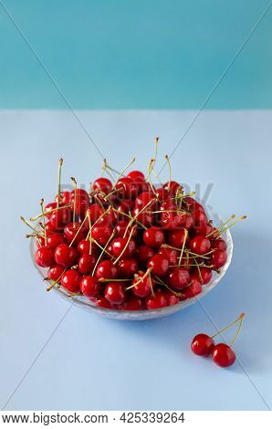 Ripe, Fresh Cherries In A Glass Bowl On A Blue Background