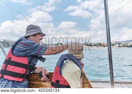 Asian Boy And Older Man, His Grandfather, In Life Jackets Trip On Pleasure Boat On The Sea.