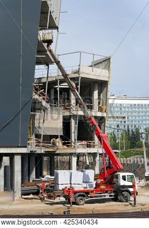 The Aerial Platform Stopped Near A Building Under Construction. The Boom With The Cradle Is Protrude