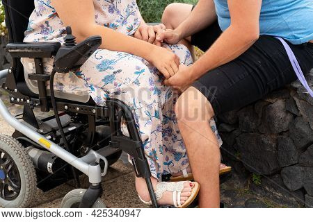 Cropped Shot Of Loving Couple, Young Man With His Disabled Girlfriend Or Wife In Wheelchair Holding