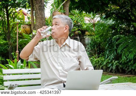 Asian Elderly Man He Uses His Laptop To Work In The Garden Of His Residence. He Was Holding A Glass