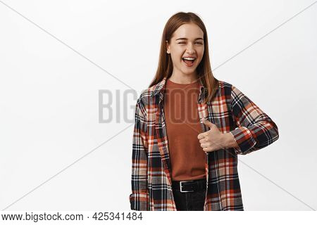 Portrait Of Cheerful Young Woman Winking And Showing Thumb Up In Approval, Agree Or Like Smth, Encou