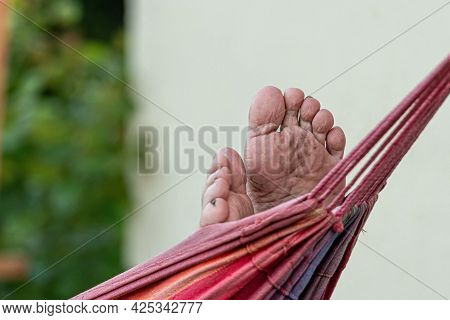 Man Is Chilling And Relaxing In The Hammock, Selective Focus, Focus On The Feet