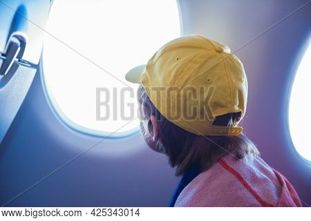 Boy Looking Clouds And Sky Outside The Plane Porthole. Teen Have Flight Looking Astonished In The Ai
