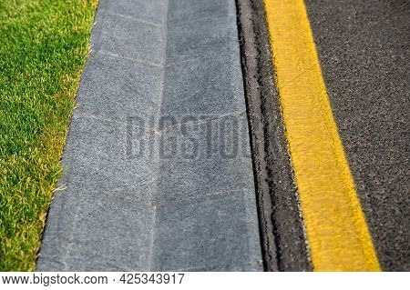 Straight Ditch Canal Concrete Hollow On The Side Of An Asphalt Road With Yellow Markings And Green G