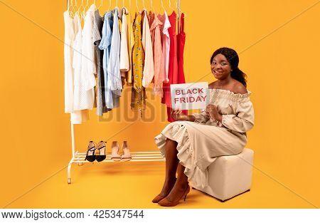 Black Lady Holding Black Friday Sign, Offering Huge Seasonal Sale, Sitting Near Clothing Rack On Ora