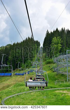 A Lift With Many Benches Takes People Up The Mountain Covered With Trees. Photo Taken In Summer, Man