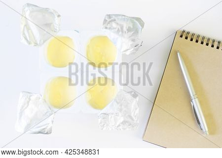 A Package Of Four Open Plastic Boxes With Fruit Yogurt On A White Background Next To A Notepad And A