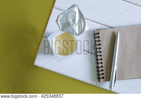 Open Plastic Box With Yogurt And Notebook With Pen On Natural Painted Boards. Golden Background. The