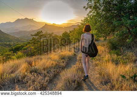 Rear View Of Beautiful Slender Young Woman Walking Alone Country Road Against Amazing Summer Landsca