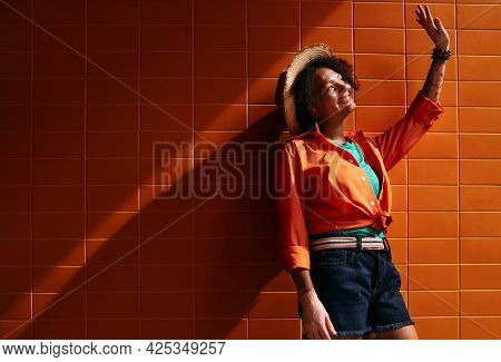 Smiling African American Woman Wearing Trendy Clothes And Straw Hat Near Orange Building Wall Stands