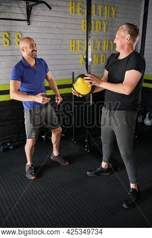 Male Personal Trainer Laughing And Enjoying Training Elderly Senior Man. Doing Weighted Medicine Bal