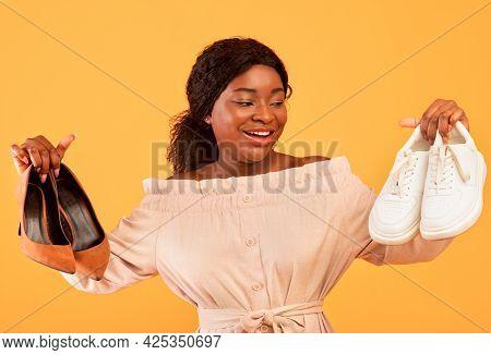 Millennial Black Female Choosing Between Elegant High-heeled Shoes And Comfy Sneakers On Orange Stud