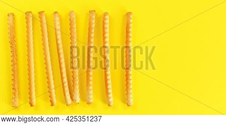 Grissini, Also Known As Breadsticks On Yellow Board, View From Above Space For Text Right Side