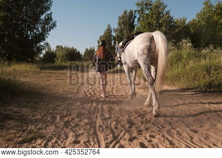 Woman In A Helmet Walks With Her Horse Along A Dusty Sandy Road, Holding Her By The Bridle, At Sunse