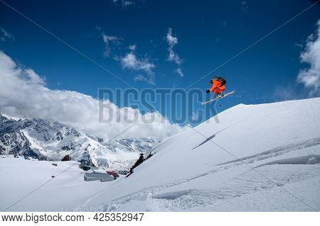 Professional Athlete Young Male Skier In An Orange Ski Suit Flies Over The Mountains After Jumping F