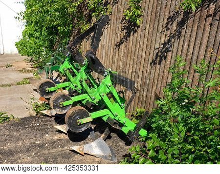 Plows Clinging To The Tractor For Plowing The Land. Farm Concept