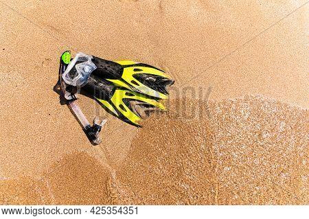 Snorkeling Equipment On The Sand With Ocean Waves Splashing The Water. Black Fins, Black Mask, Snork
