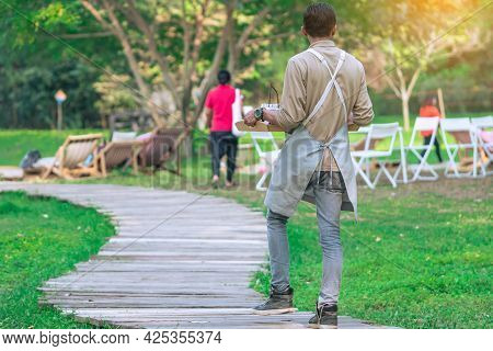 Back View Of Asian Male Waiter Carry Food And Beverages Along Garden Paths To Serve Customers While