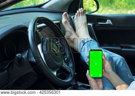 Young Female Driver In Blue Jeans And Barefoot Holds Smart Phone With Green Screen Inside Car. Conce