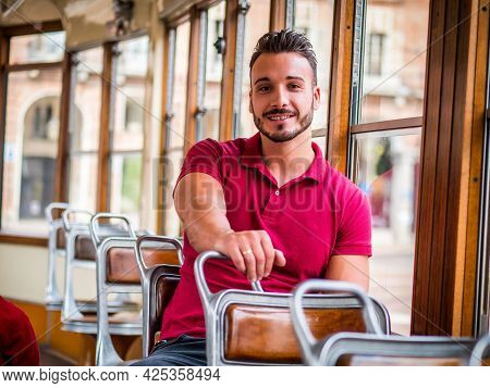 Young Handsome Man Riding On Tram Or Old Bus In City