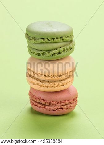 Stack of three macarons of pistachio, vanilla and raspbery flavor on pastel green background