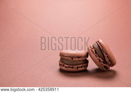 Chocolate flavor French macaron cookies closeup on background of a similar brown colour with copy space