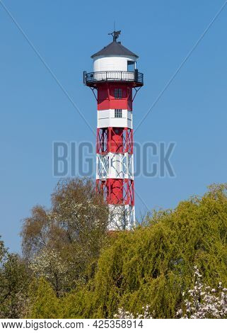 Lighthouse of Grünendeich at Altes Land region, Germany, trees in foreground