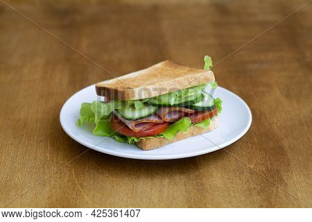 Sandwich With Ham And Vegetables.tasty Sandwich With Ham, Green Salad, Cucumbers And Tomatoes On The