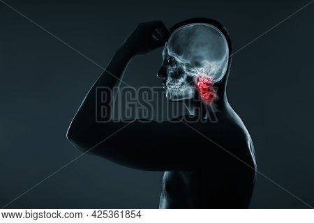 X-ray Of A Man's Head. Medical Examination Of Head Injuries. The Neck Spine Is Highlighted By Red Co