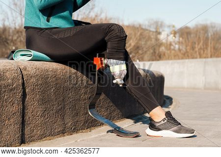 Cropped image of a young healthy sportswoman with prosthetic leg resting sitting outdoors drinking water from a bottle
