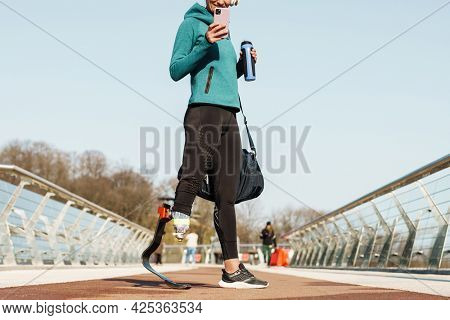 Cropped image of a young healthy sportswoman with prosthetic leg standing holding mobile phone and bottle of water outdoors drinking water from a bottle