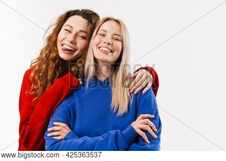 Two smiling young white women friends wearing sweatshirt standing posing isolated over white background hugging looking at camera